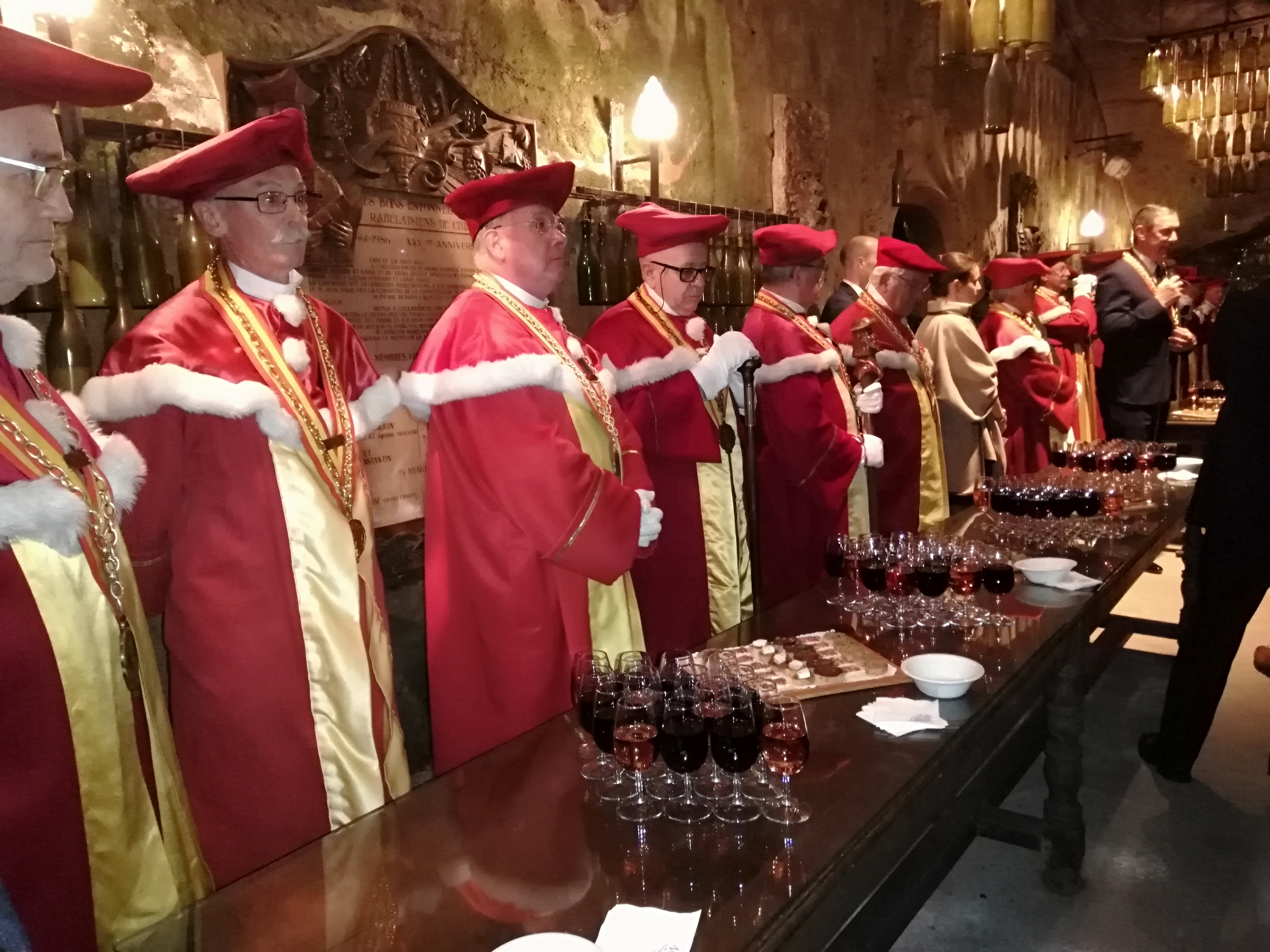 Red robes and Chinon wine, in a cave
